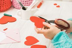 Valentine's day theme. Female hands cut the heart out of the pap. Er. Packed gifts, tools on a battered wooden table. Workplace for the preparation of handmade stock photography