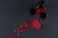 Valentine`s day theme. Wine bottle and two wineglasses with red hearts on a dark background. Love card concept with copy space, Valentine`s day theme. Shot from Royalty Free Stock Photography