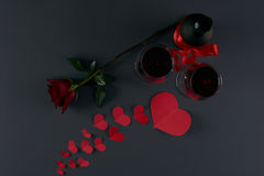 Valentine`s day theme. Wine bottle and two wineglasses with red hearts and rose flower on a dark background. Love card concept, Valentine`s day theme. Shot from Royalty Free Stock Photo