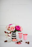 Valentine`s Day Treats With Pink Flowers. A collection of Valentine`s Day treats with pink flowers in a black and white vase Royalty Free Stock Image