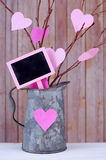 Valentine's Day. Valentine tree made out of bare twigs and paper cutout pink hearts in a vintage tin pitcher stock photo