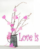 Valentine's Day. Valentine tree made out of bare twigs and paper cutout pink hearts in a vintage tin pitcher royalty free stock image