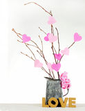 Valentine's Day. Valentine tree made out of bare twigs and paper cutout pink hearts in a vintage tin pitcher royalty free stock images
