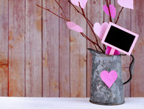 Valentine's Day. Valentine tree made out of bare twigs and paper cutout pink hearts in a vintage tin pitcher in front of wood background with copyspace stock images