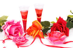 Valentine`s day. Two glasses, candles and roses  isolated on white background Stock Photos