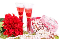 Valentine`s day. Two glasses, flowers, colorful pearls necklaces and gift box on white background Royalty Free Stock Photography