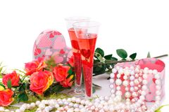 Valentine`s day. Two glasses, flowers, colorful pearls necklaces and gift box on white background Royalty Free Stock Image