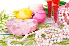 Valentine`s day. Two glasses, flowers, colorful pearls necklaces and gift box on white background Stock Photo