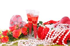 Valentine`s day. Two glasses, flowers, colorful pearls necklaces and gift box on white background Royalty Free Stock Photo