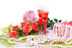 Valentine's day. Two glasses, flowers, colorful pearls necklaces and gift box on white background Royalty Free Stock Photography