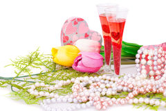 Valentine's day. Two glasses, flowers, colorful pearls necklaces and gift box on white background Stock Image