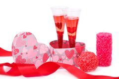 Valentine`s day. Two glasses with red candle, gift box and red ribbon isolated on white background Stock Images