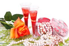 Valentine`s day. Two glasses, rose, colorful pearls necklaces and gift box on white background Stock Photo