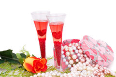 Valentine's day. Two glasses, rose, colorful pearls necklaces and gift box on white background Stock Photography