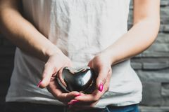 Female hands hold a metal heart, a concept of love. stock photos