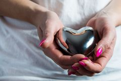 Female hands hold a metal heart, a concept of love. stock image