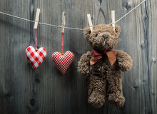 Valentine's Day wallpaper - Teddy Bear hanging with textile hearts Stock Photo