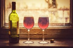 Valentine`s Day, wedding anniversary, betrothal, Two glasses of. Bottle of red wine and glasses on an old stone window sill. Still lifer stock photos