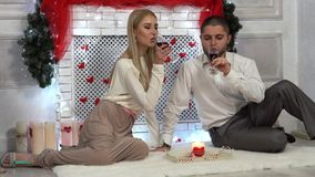 Valentine`s Day, Wedding footage of beautiful Young Couple drinking red wine in romantic interior. Man and Woman relaxing and drinking Wine sitting on the floor stock video footage