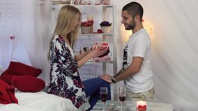 Valentine`s Day, Wedding footage of man giving a gift to his girlfriend in romantic interior. stock video footage