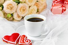 Valentine`s day. Wedding, mother`s day. A Cup of coffee and two gingerbread heart on a background of flowers and gifts.  royalty free stock images