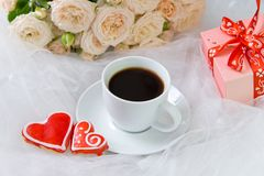 Valentine`s day. Wedding, mother`s day. A Cup of coffee and two gingerbread heart on a background of flowers and gifts.  Stock Images