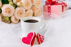 Valentine`s day. Wedding, mother`s day. A Cup of coffee and two. Gingerbread heart on a background of flowers and gifts Royalty Free Stock Photos