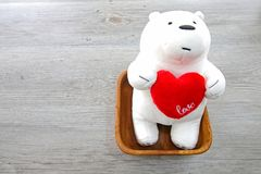 Valentine`s Day White Bear holding a red heart on wooden background. Valentines Day White Bear holding a red heart on wooden background stock photos