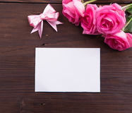 Valentine's Day: White empty paper card, pink roses, and bow ribbons Royalty Free Stock Images