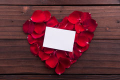 Valentine's Day: White empty paper card and red love shaped rose petals Royalty Free Stock Photos