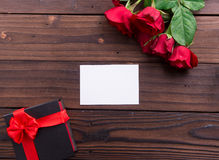 Valentine's Day: White empty paper card, red roses, and box gift with ribbons Royalty Free Stock Photography