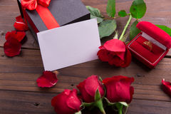 Valentine's Day: White empty paper card, red roses, gold ring and box gift with ribbon Royalty Free Stock Photos