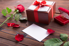 Valentine's Day: White empty paper card, red roses, gold ring and box gift with ribbon Royalty Free Stock Image