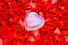 Valentine`s day. A white glass heart lies on red-ruby crystals in the middle. Macro photography stock image