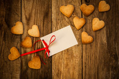 Valentine`s day. On the White Isolated Letter and Gingerbread Cookies in the Shape of Heart at Valentine Day. On the wooden background Royalty Free Stock Photo
