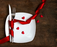 Valentine`s day, white plate, knife, fork, red ribbon Stock Photos