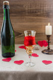 Valentine`s Day. wine, candles, small heart. On the wooden background Stock Image