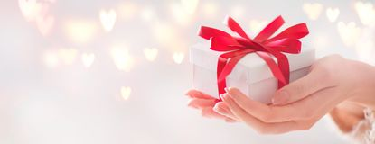 Valentine`s Day. Woman holding gift box with red bow stock photos