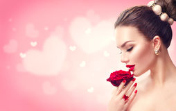Valentine`s day. Woman with red rose. Fashion model girl face portrait stock photography