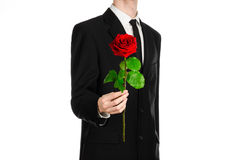 Valentine's Day and Women's Day theme: man's hand in a suit holding a red rose isolated on white background in studio Stock Photos