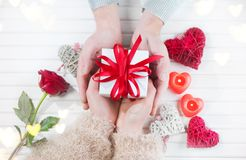 Valentine`s Day. Young couple hands holding gift box over white wooden background. Love concept. Top view Stock Image