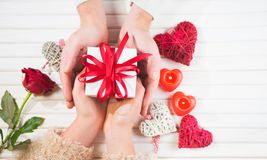 Valentine`s Day. Young couple hands holding gift box over white wooden background. Love concept. Top view. Flatlay royalty free stock photos