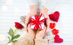 Valentine`s Day. Young couple hands holding gift box over white wooden background. Love concept. Top view. Flatlay stock image