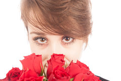 Valentine's Day. A young woman looks at you while holding a bunch of roses Royalty Free Stock Photos