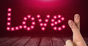 Valentine`s fingers love couple and Love text glowing neon light bulbs over wooden floor. Digital composite of Valentine`s fingers love couple and Love text Stock Photos