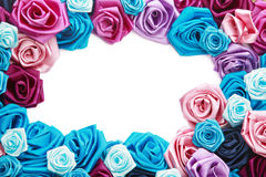 Valentine's frame. Of blue, vinous, pink and turquois handmade silk roses on white background with copy space in center Stock Photos