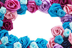 Valentine's frame. Of blue, vinous, pink and turquois handmade silk roses on white background with copy space in center Royalty Free Stock Image