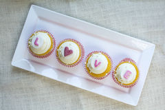 Valentine's french vanilla cupcake with colorful fondant love al. Valentine's french vanilla cupcakes with love alphabet letter gum paste topper in white square stock image