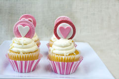 Valentine's french vanilla cupcake with colorful heart fondant t. Valentine's french vanilla cupcakes with heart gum paste topper in white square ceramic plate stock photo