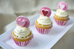 Valentine's french vanilla cupcake with heart gumpaste topper. Valentine's french vanilla cupcakes with heart gum paste topper in white square ceramic plate stock image